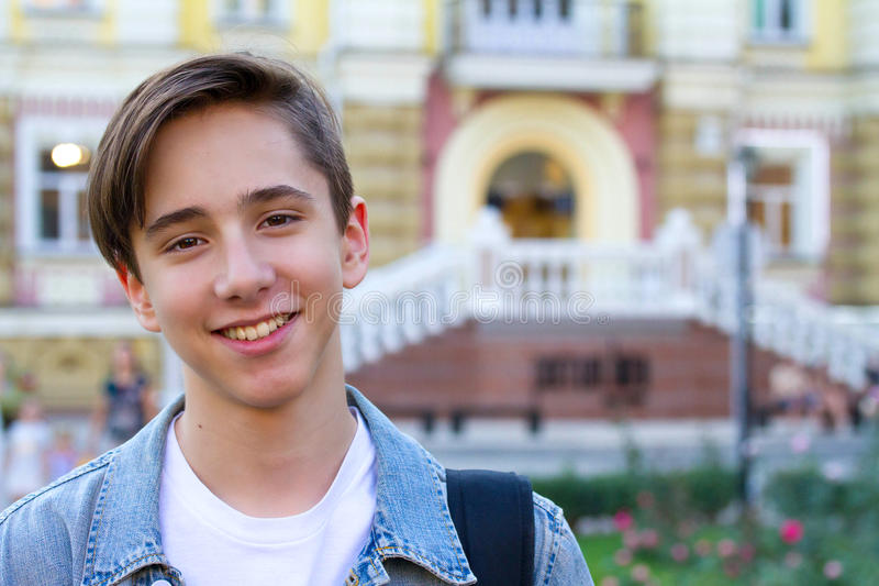 Outside portrait of teen boy. Handsome teenager carrying backpack on one shoulder and smiling. Outside portrait of teen boy. Handsome teenager carrying backpack royalty free stock photography