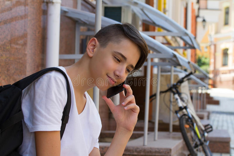 Outside portrait of teen boy. Handsome teenager carrying backpack on one shoulder and smiling, speaking by phone. Outside portrait of teen boy. Handsome royalty free stock photo