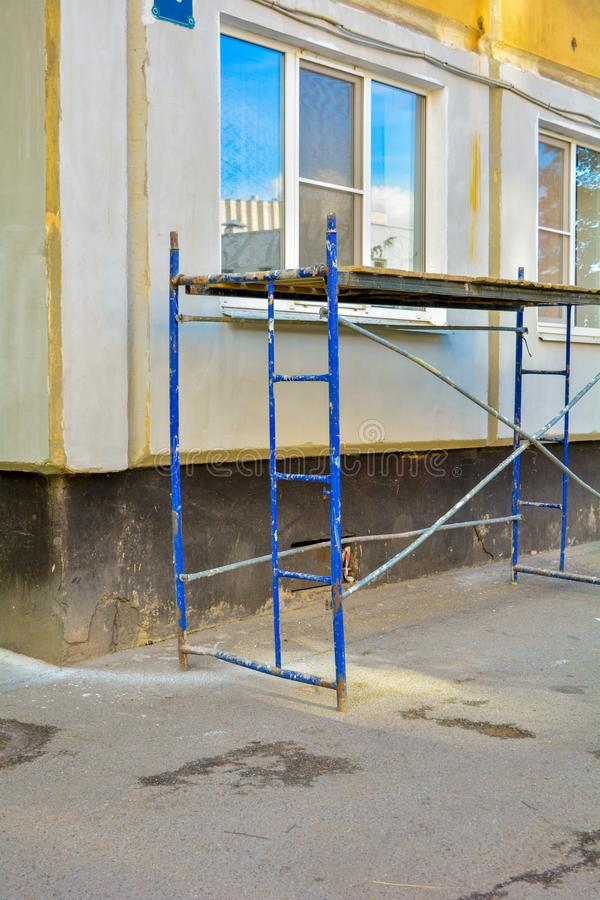 Outside repair, renovation of apartment house, blue paint metal scaffold tower. Outside repair and renovation of a apartment house using blue paint metal small stock photo
