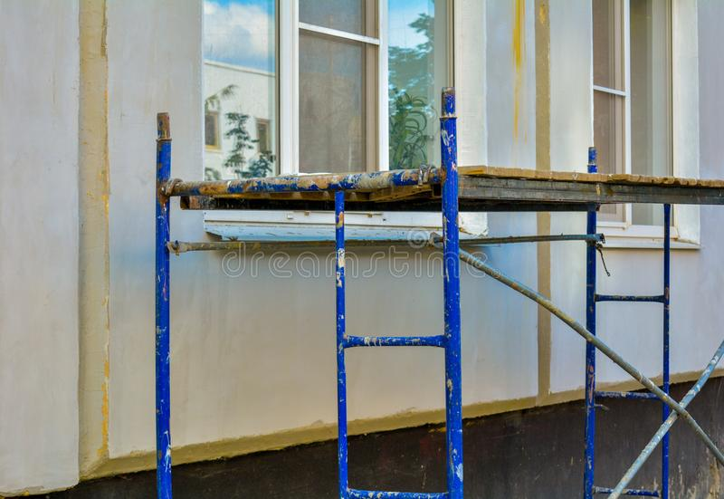 Outside repair, renovation of apartment house, blue paint metal scaffold tower. Outside repair and renovation of a apartment house using blue paint metal small stock image