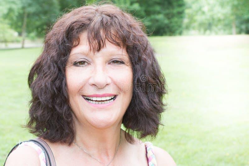 Outside smiling nice looking elderly senior woman portrait. Oute smiling nice looking elderly senior woman portrait with green garden park in the background royalty free stock photos