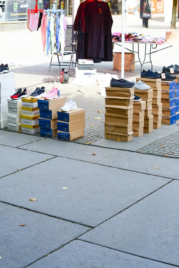 Outside street market Shoe seller. With their shoes in the carton, in the square. copy space dayligtht royalty free stock photography