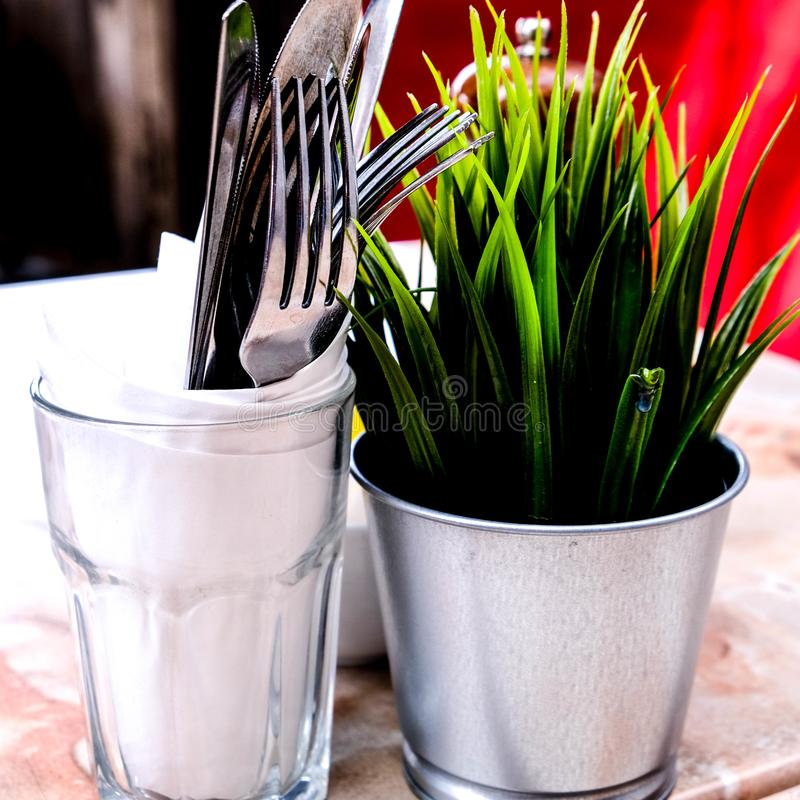 Outside Table Setting with an Artificial Plant and Eating Utensils royalty free stock images