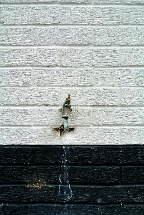 Outside tap. The outside tap on the black and white wall stock photos