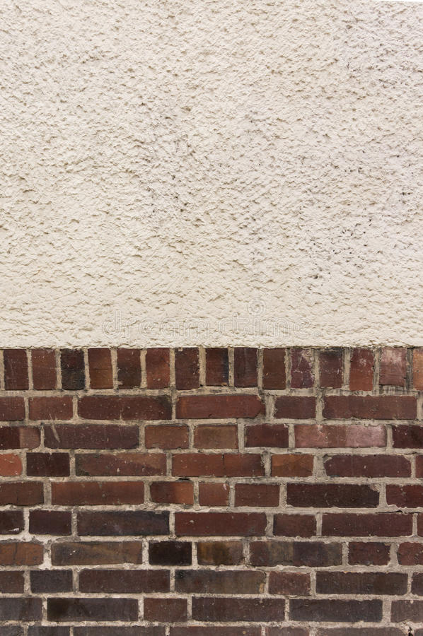 Outside wall with plastered top on red clinker brick bottom. Background pattern texture royalty free stock photo