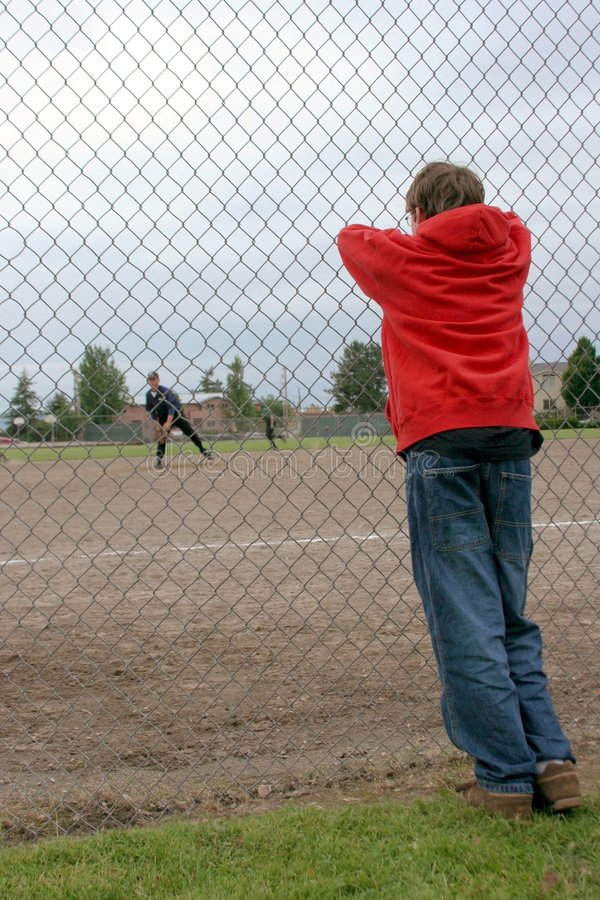 The Outsider. A teenage boy watching a game from the sidelines stock image