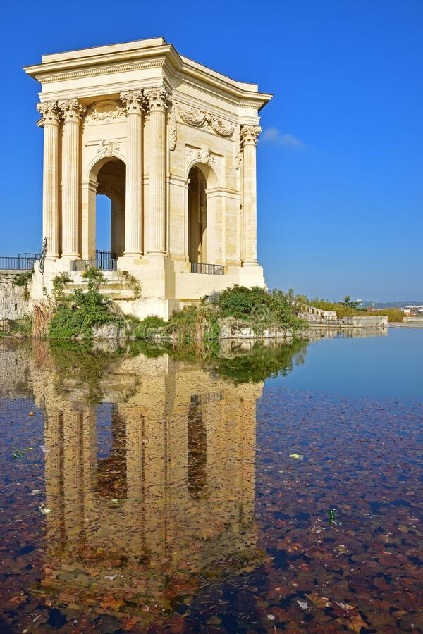 Side view full water reflection of bassin principal du Peyrou, water tower at Promenade du Peyrou in Montpellier, southern France. On the outskirts of the stock photography