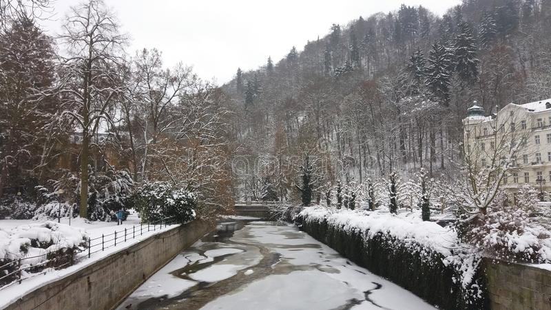 Snowy and icy landscape in Bohemia. Snow-covered buildings, shrubs and trees on mountain slopes; the river Tepla, heated by thermal springs, is partially ice royalty free stock images