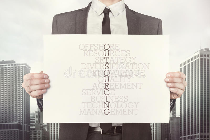 Outsourcing crossword concept on paper stock photo