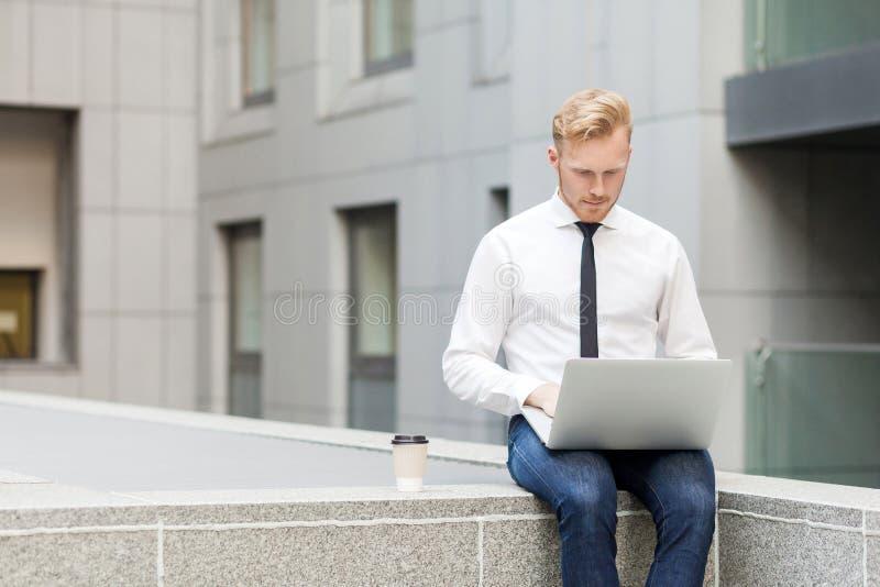 outsourcing Hombre principal rojo que trabaja tiempo de verano al aire libre de i imagen de archivo