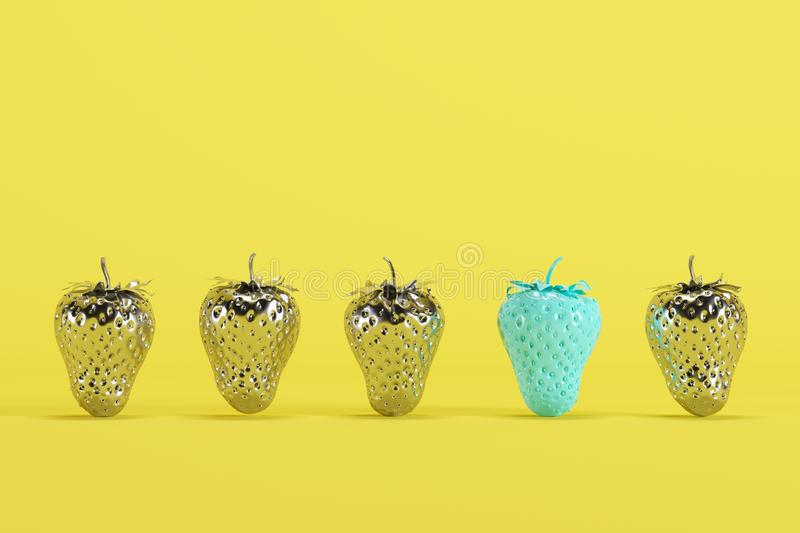 Outstanding blue painted strawberry among silver painted strawberries on yellow background stock photography