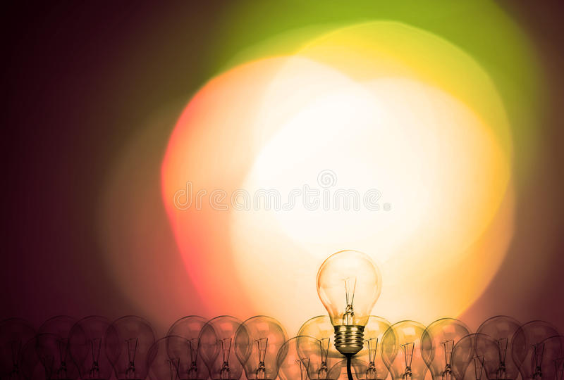 Outstanding creative idea background concept . one Light bulb glowing among a group light bulbs. royalty free stock photography
