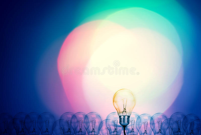 Outstanding creative idea background concept . one Light bulb glowing among a group light bulbs. stock photos