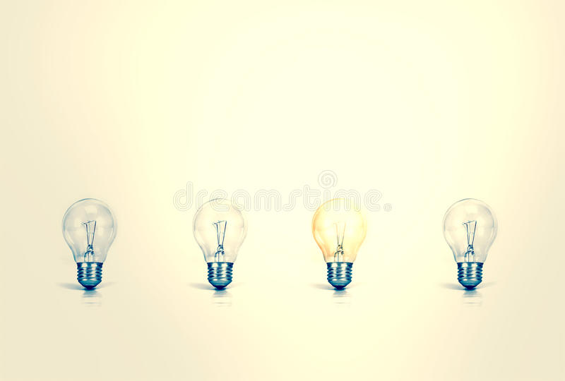 Outstanding creative idea background concept . one Light bulb glowing among a group light bulbs.vintage color tone stock photography