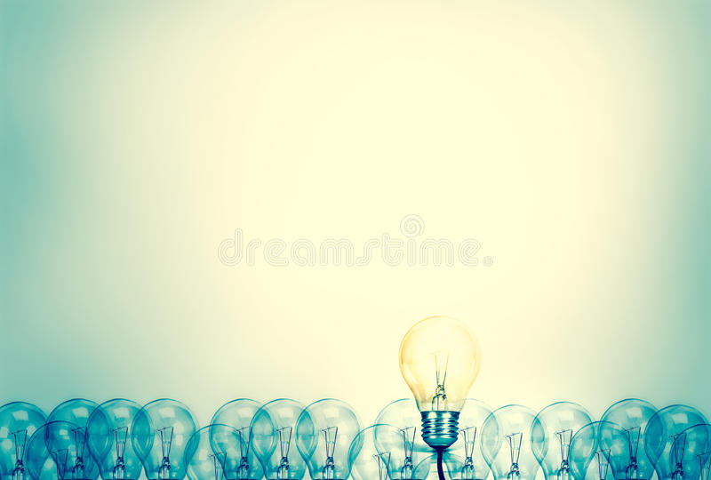 Outstanding creative idea background concept . one Light bulb glowing among a group light bulbs.vintage color tone stock photo