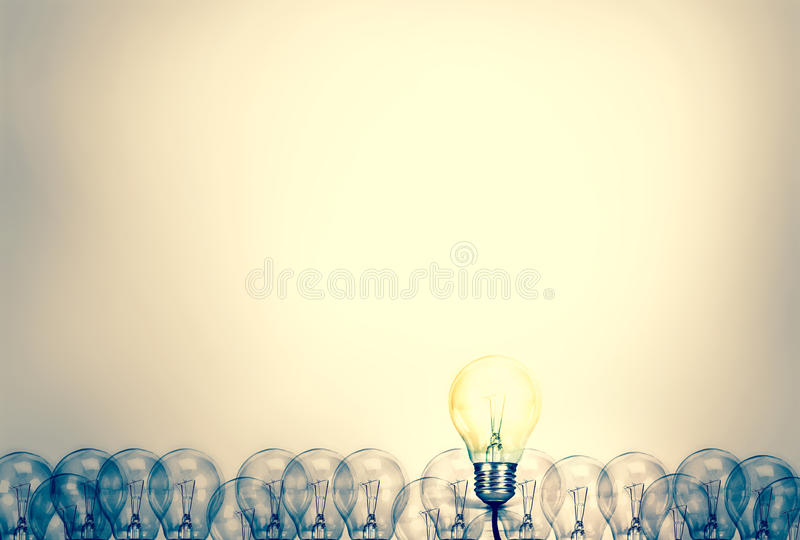 Outstanding creative idea background concept . one Light bulb glowing among a group light bulbs.vintage color tone stock images