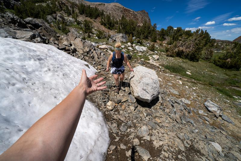 Giving another hiker a helping hand through the snow in Eastern Sierra backcountry stock photo