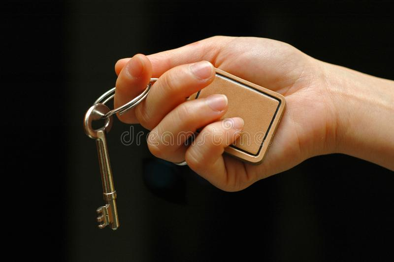 Outstretched hand holding key stock image