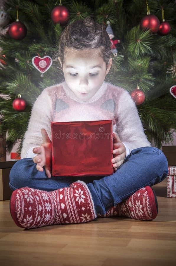 Ouverture de petite fille qu'il se présentent sous l'arbre de Noël photos stock