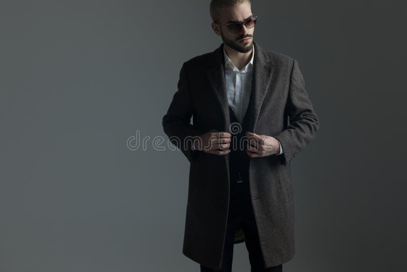 Ouverture ou fermeture blonde debout d'homme de son longcoat photographie stock