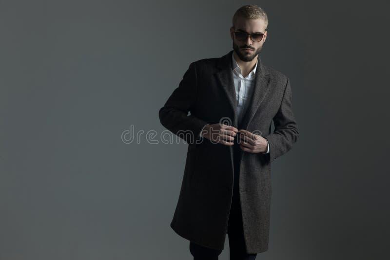 Ouverture ou fermeture blonde debout d'homme de son longcoat image libre de droits