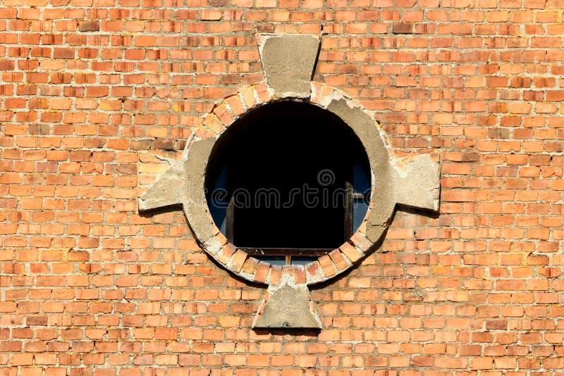 Ouverture ronde de fenêtre avec le verre partiellement cassé et cadre décoratif de tuiles de briques rouges sur le vieux complexe image libre de droits