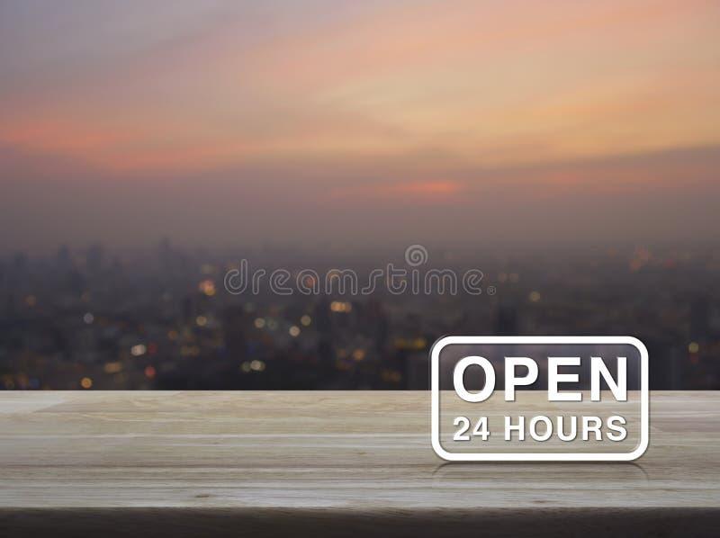 Ouvrez 24 heures d'icône sur la table en bois au-dessus de la tache floue du paysage urbain sur la guerre photographie stock libre de droits