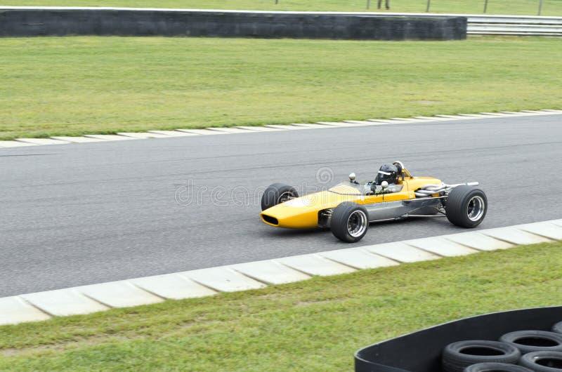 Ouvrez l'entraînement de voiture de course jaune d'habitacle sur la voie photographie stock