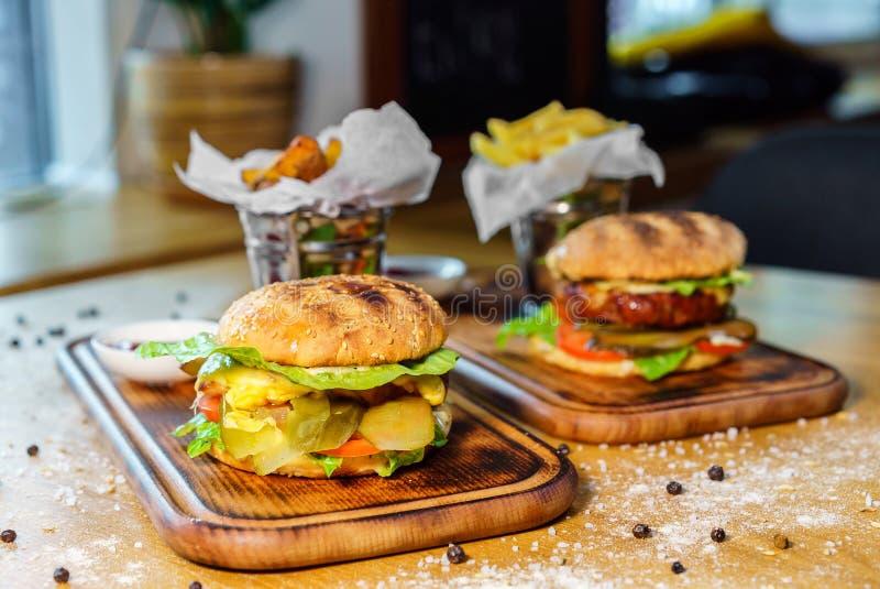 Ouvrez l'hamburger et les pommes frites de boeuf sur la table en bois photos stock