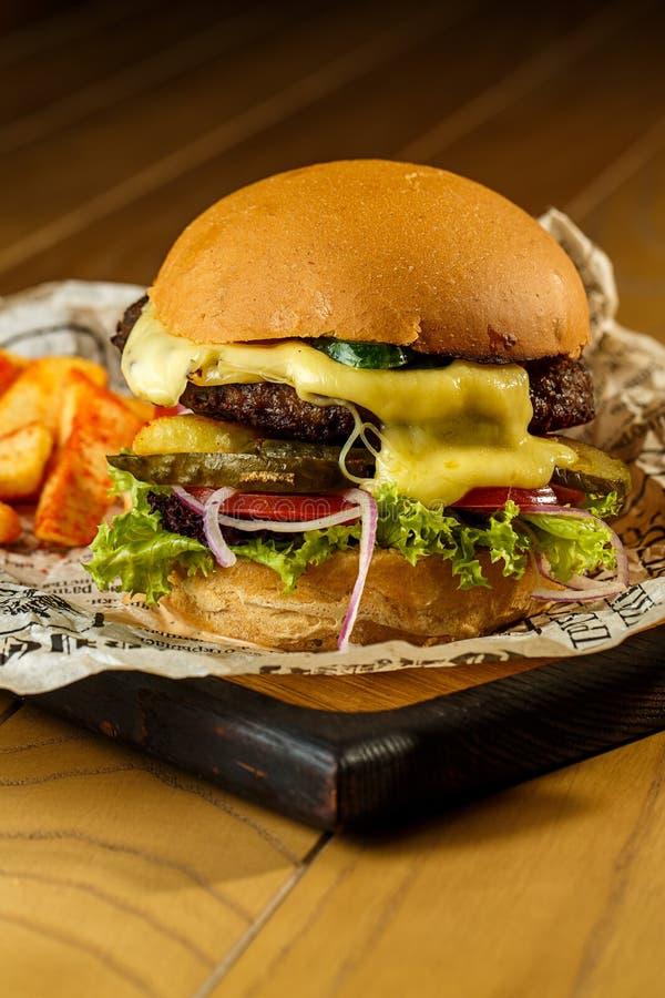 Ouvrez l'hamburger et les pommes frites de boeuf sur la table en bois image libre de droits