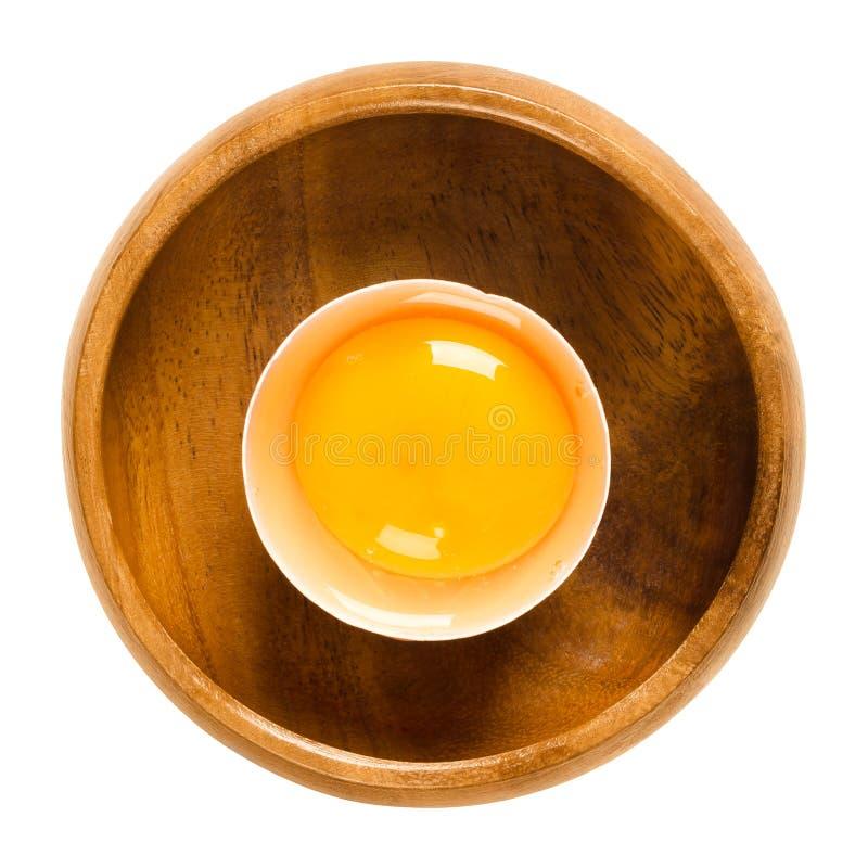 Ouvrez l'oeuf cru de poulet dans la cuvette en bois au-dessus du blanc photographie stock