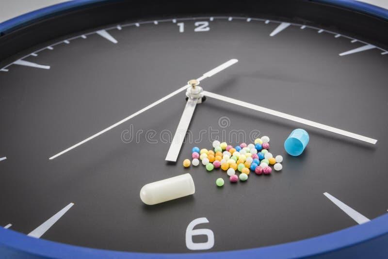 Ouvrez la pilule rouge de capsule avec la drogue de couleur de boule sur l'horloge noire photos stock