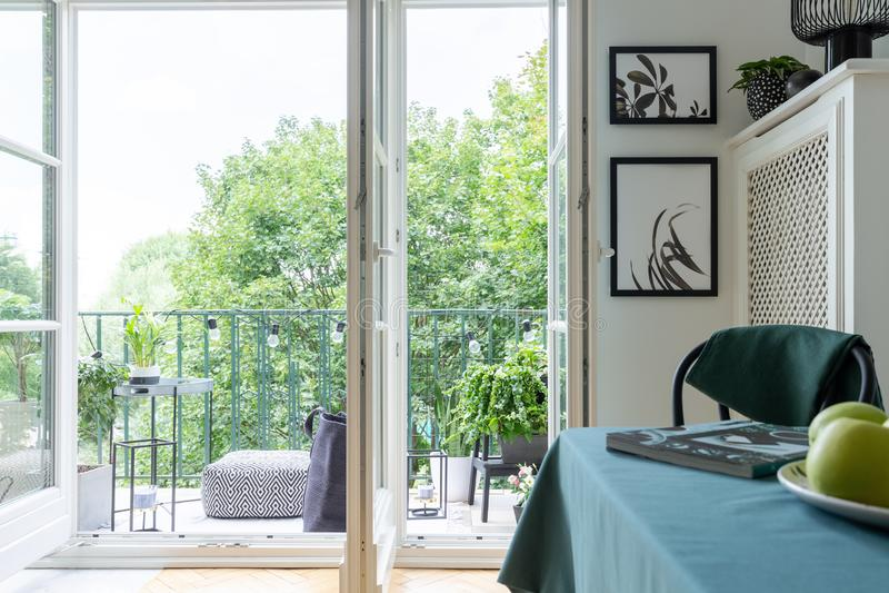 Ouvrez la porte de balcon avec vue sur des arbres Pouf et table sur un balcon images stock