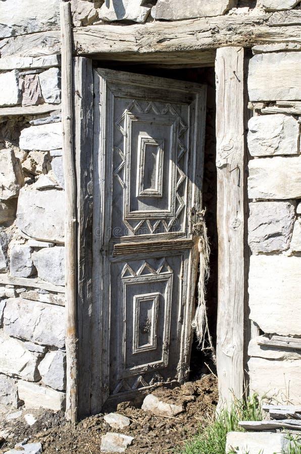 Ouvrez la porte en bois avec des ornements sur l'étable dans la vieille maison en pierre image stock