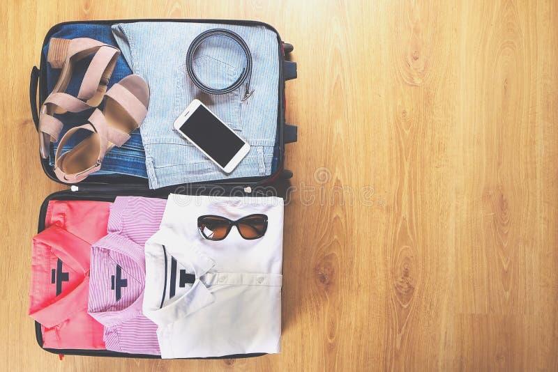 Ouvrez la valise avec les vêtements et les accessoires femelles à la mode sur la vue supérieure de plancher en bois, l'espace de  photo libre de droits