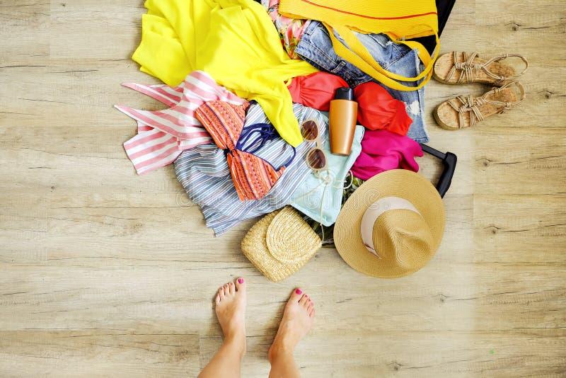 Ouvrez la valise avec la pile de l'habillement dévoilé sur le plancher Emballage de femme pour le concept tropical de vacances C  images stock