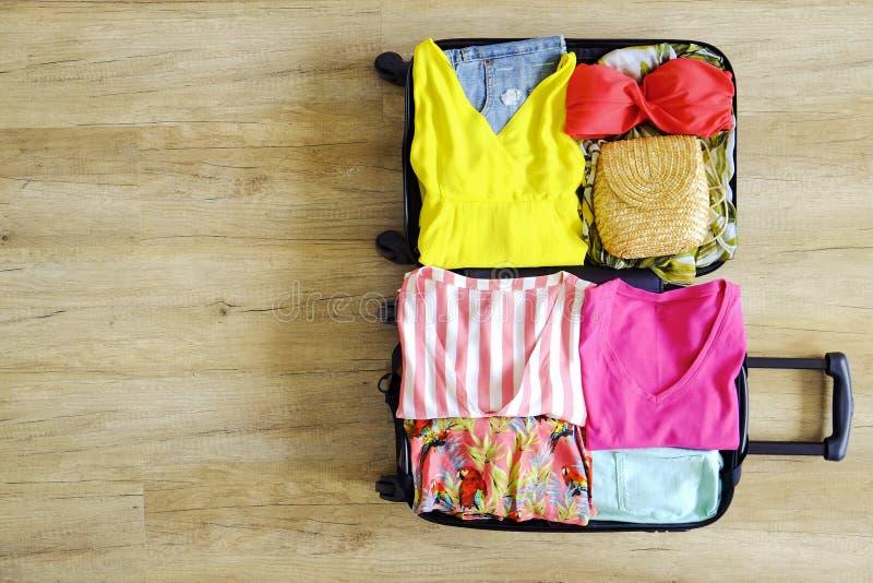 Ouvrez la valise entièrement emballée avec l'habillement et les accessoires pliés du ` s de femmes sur le plancher Emballage de f photos libres de droits