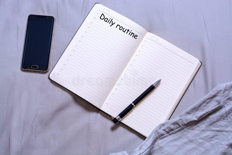 Ouvrez le bloc-notes avec le stylo noir avec l'inscription et l'endroit pour des mensonges des textes sur le lit avec un smartpho image stock