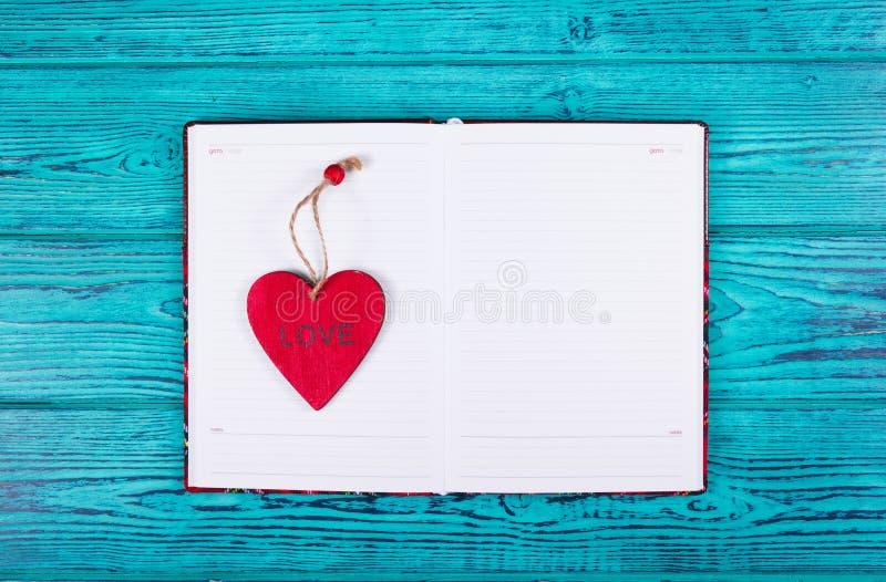 Ouvrez le carnet avec des pages propres et un coeur rouge Calibres et milieux photographie stock libre de droits