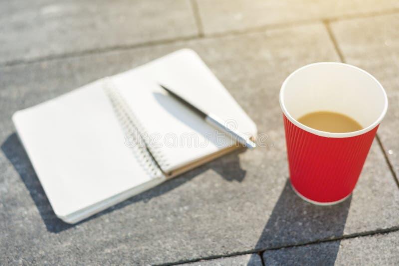 Ouvrez le carnet avec les pages vides, le stylo et la tasse de café sur le pavé gris image libre de droits
