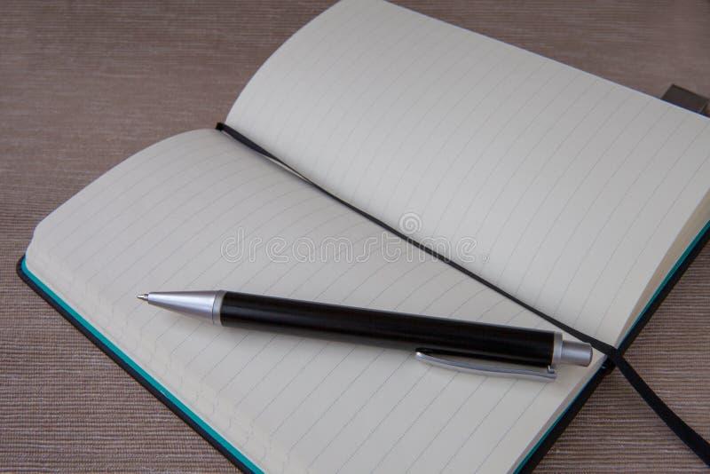Ouvrez le carnet et le stylo noir photo stock