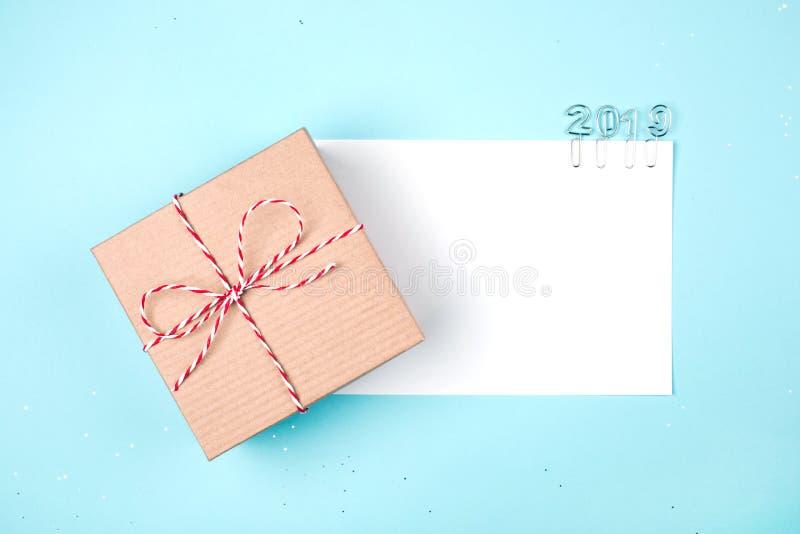 Ouvrez le giftbox avec la feuille blanche vide de papier et de 2019 agrafes sur le fond bleu images libres de droits