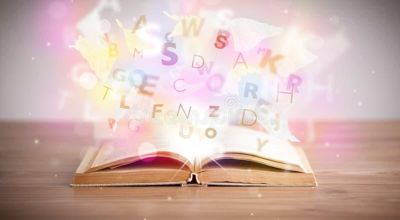 Ouvrez le livre avec les lettres rougeoyantes sur le fond concret photographie stock