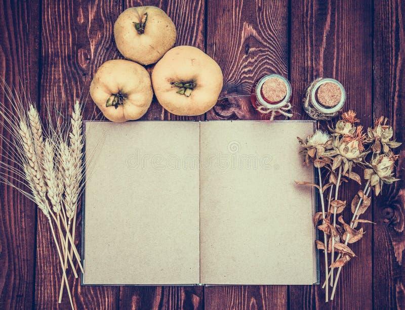 Ouvrez le livre avec les pages vides sur un fond d'automne Le coing, blé, a séché des herbes, des bouteilles et un livre ouvert s image stock