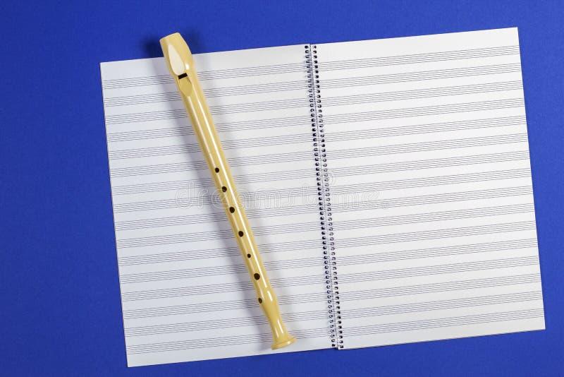 Ouvrez le livre d'exercice avec des pentagones étoilés et la cannelure d'instrument de musique sur le fond bleu images libres de droits