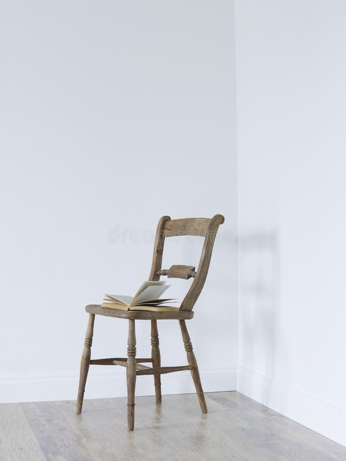 Ouvrez le livre sur la chaise dans le coin vide de chambre images libres de droits