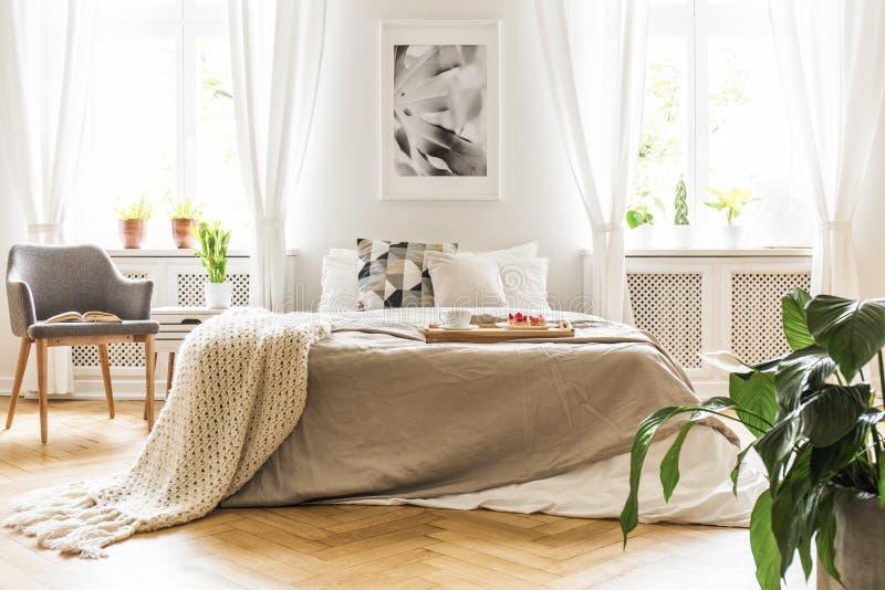 Ouvrez le livre sur un fauteuil gris et en bois par un lit confortable avec des breakfas photos libres de droits
