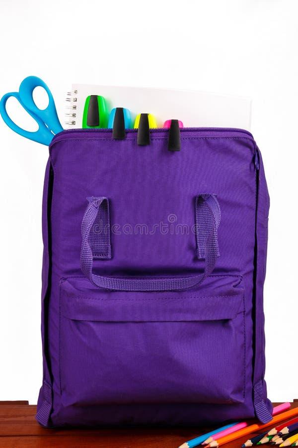 Ouvrez le sac à dos pourpre avec des fournitures scolaires sur la table en bois De nouveau à Fin vers le haut images libres de droits
