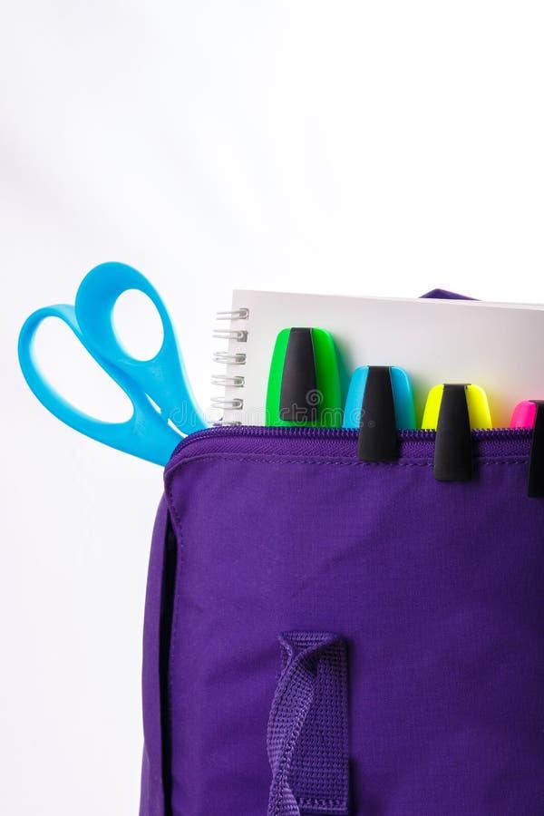 Ouvrez le sac à dos pourpre avec des fournitures scolaires sur le fond blanc De nouveau à Fin vers le haut photographie stock libre de droits