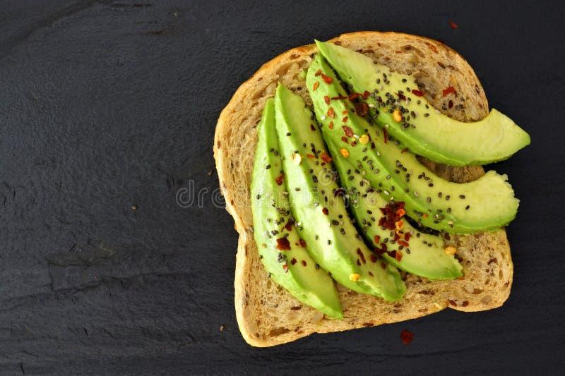 Ouvrez le sandwich à avocat avec des graines de chia sur l'ardoise foncée photographie stock libre de droits